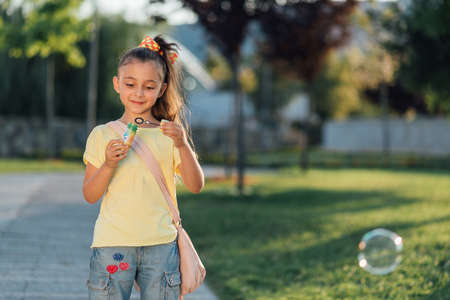 staying: little girl is staying and blow bubbles Stock Photo