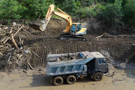 convulsión: excavadora despeja el camino de deslizamiento de tierra