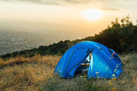tent city: blue tent on a hill near the city in the morning