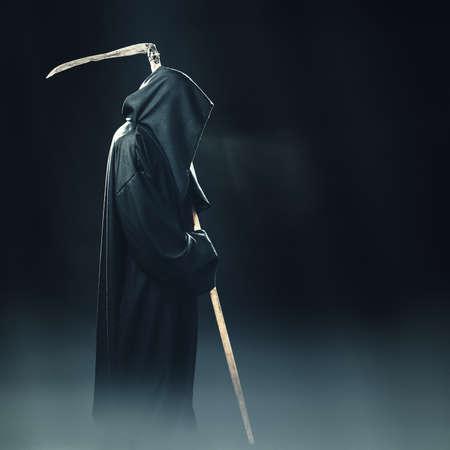 dood met zeis staande in de mist bij nacht