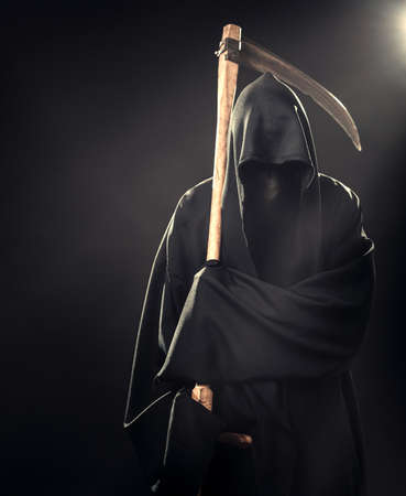 grim reaper: death with scythe standing in the fog at night Stock Photo