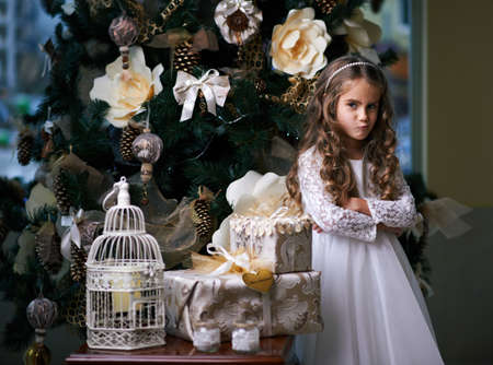 disgruntled: beautiful girl grimaced near Christmas gifts