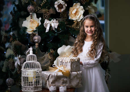 toothless: Beautiful toothless girl in a white dress laughing near the Christmas tree Stock Photo