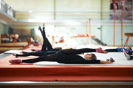girl posing: She kneads his back in training rhythmic gymnastics