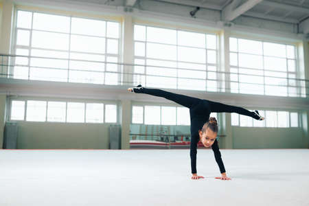 female gymnast: little gymnast standing on hand doing the splits