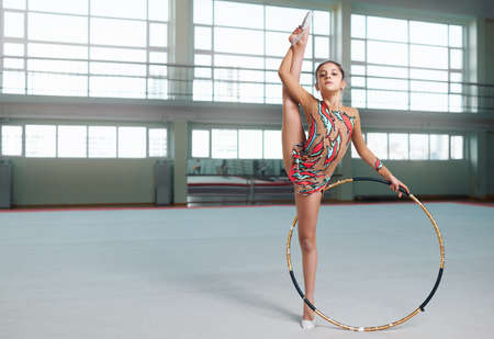 stretchy: little gymnast in a nice suit doing stretching with hoop