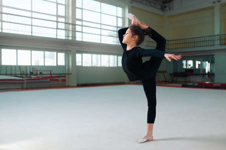stretchy: girl gymnast in a sweatsuit doing exercises the balance