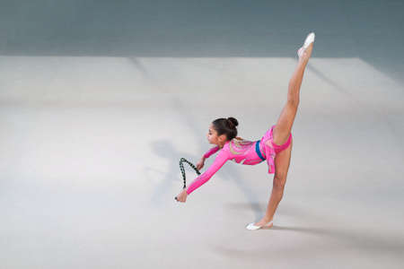 stretchy: gymnast in a nice suit doing exercises with skipping rope