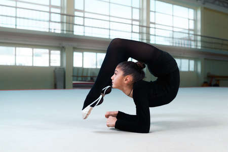 stretchy: gymnast performs a back bend on the floor Stock Photo