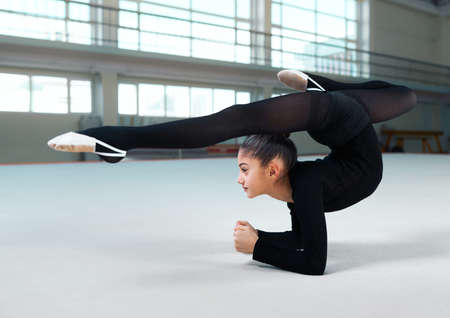 stretchy: Side view of little girl practicing gymnastic in gym-hall