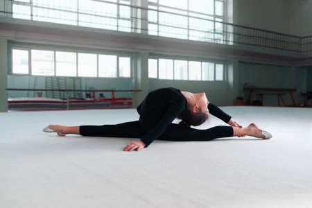 gimnasia: ni�a gimnasta en una sudadera haciendo ejercicios de estiramiento