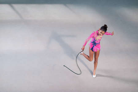stretchy: gymnast in a beautiful dress dancing with a rope