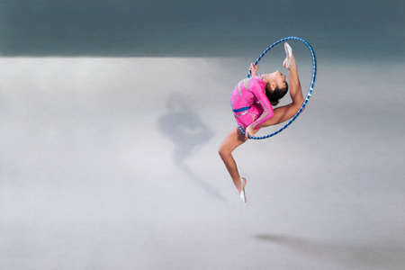 young gymnast: gymnast in a beautiful pink dress with a hoop in a jump Stock Photo
