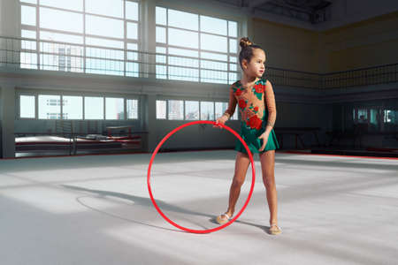 acrobat gymnast: Girl gymnast with a hoop looking away