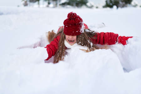 Little laughing girl rolling in snowdrift. Wintertime. Eyes covered with hat.