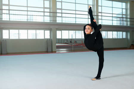 plasticity: beautiful girl in the hall of rhythmic gymnastics makes the balance