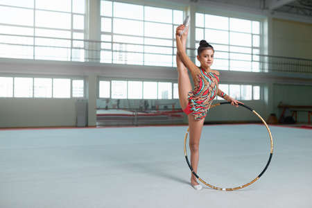 stretchy: Little girl in beautiful dress doing exercise with hoop, looking at camera