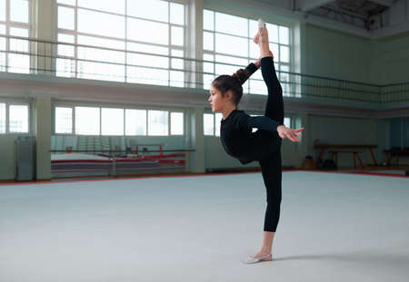acrobat gymnast: girl gymnast in a sweatsuit doing exercises the balance
