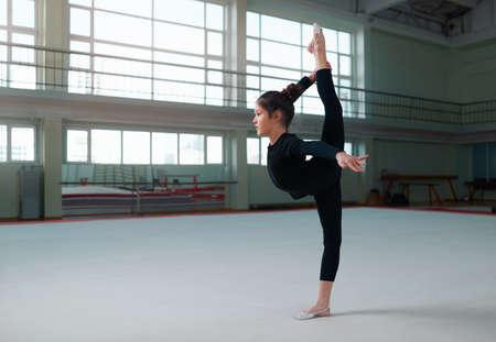 gimnasia: ni�a gimnasta en un hacer sweatsuit ejerce el equilibrio