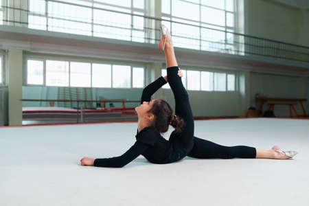rhythmic gymnastics: girl gymnast in a sweatsuit doing stretching exercises Stock Photo