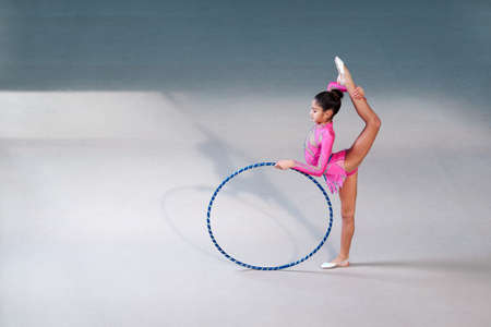stretchy: gymnast in a beautiful pink suit doing hoop exercise