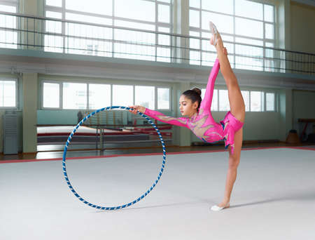 stretchy: Little girl in beautiful gymnastic dress doing exercise with hoop