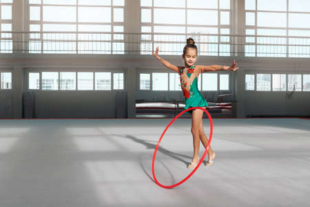 stretchy: Little girl in beautiful dress dancing with hoop in gym-hall Stock Photo