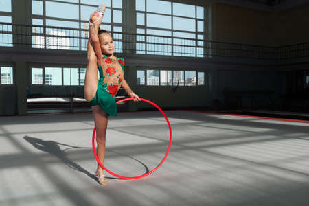 stretchy: Little girl doing exercise with hoop. Shadows on floor