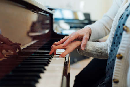helps: music teacher helps the student to play correctly
