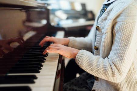 tocando el piano: manos niña que juega el primer piano de