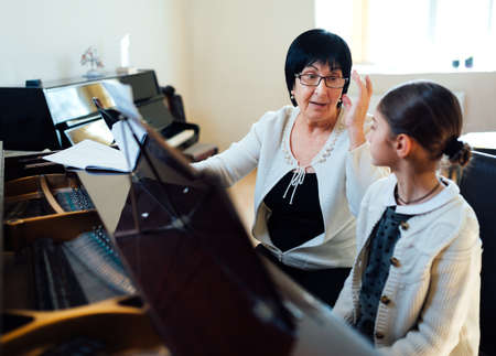 piano lesson: teacher and pupil at the lesson piano
