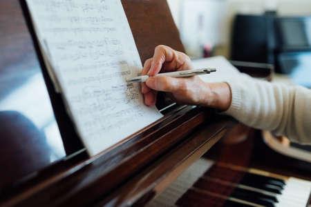 persona escribiendo: escribir notas sobre la hoja de música de primer plano