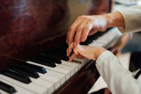 pianist: hand of an experienced pianist, music teacher helping young students