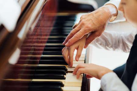 pianista: mano de un pianista experimentado, profesor de música ayudar a los estudiantes jóvenes