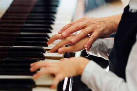 profesor de música ayuda al estudiante a reproducir correctamente Foto de archivo