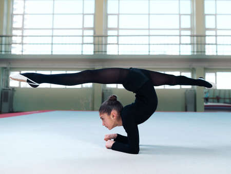 stretchy: Flexible girl standing on  hands and do the splits
