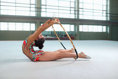 plasticity: Little girl in beautiful gymnastic dress doing exercise with hoop on floor Stock Photo
