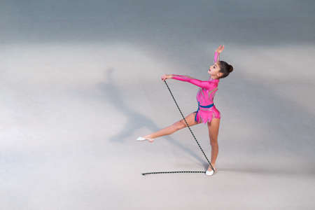 gymnast: Little girl in pink gymnastic dress doing exercise with gymnastic rope in gym-hall