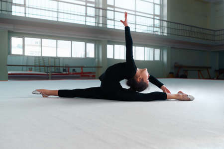 stretchy: girl gymnast in a sweatsuit doing stretching exercises Stock Photo