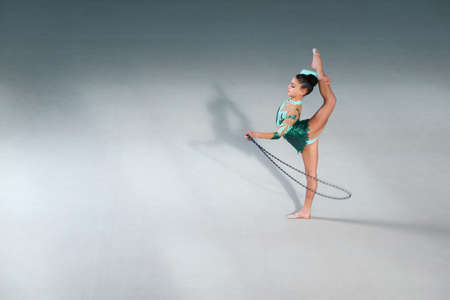 stretchy: gymnast in a beautiful green costume performs exercises with a skipping rope
