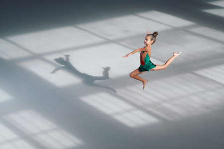 plasticity: little girl jumping gymnast trains in the sports school