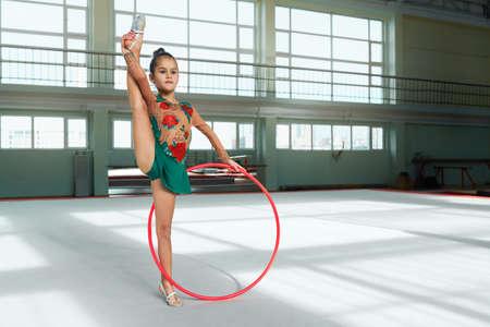 Mooi meisje turner presteert met de hoepel stretch