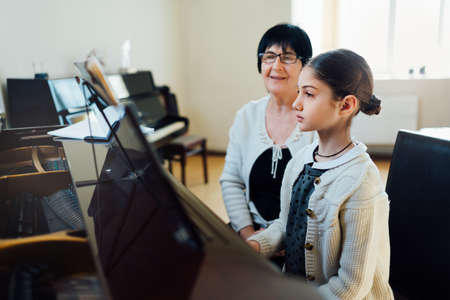grand child: piano lessons at a music school, teacher and student.