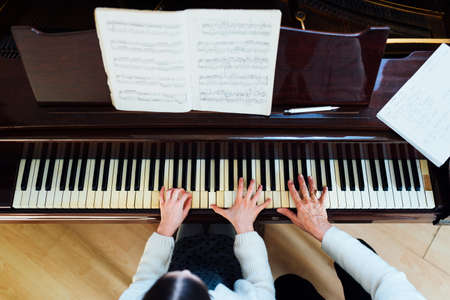 piano lessons at a music school, teacher and student. top view