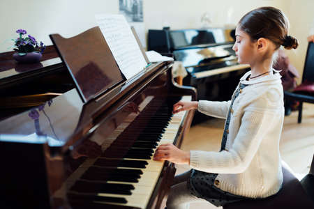 grand kids: beautiful schoolgirl playing piano at the music school