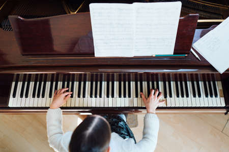 grand kid: girl playing the piano top view Stock Photo