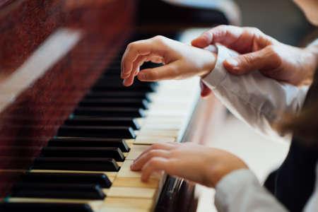tocando el piano: experimentado la mano de piano maestro ayuda al estudiante, primer plano Foto de archivo