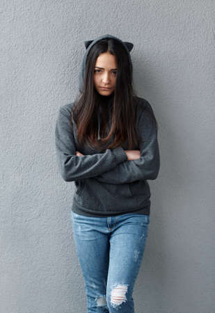 offended: offended  black-haired girl in hoodie looking at camera. Wall background. Stock Photo