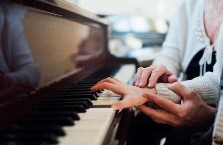 aprendizaje: experimentada mano del profesor de música antigua ayuda a la pupila niño Foto de archivo