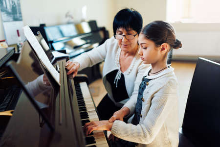 a music teacher with the pupil at the lesson piano Foto de archivo